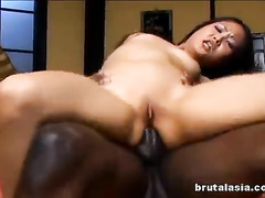 Skinny Asian slides pussy and ass on the black rod