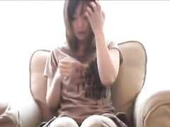 Adorable Japanese babe is sitting on couch and getting seduced